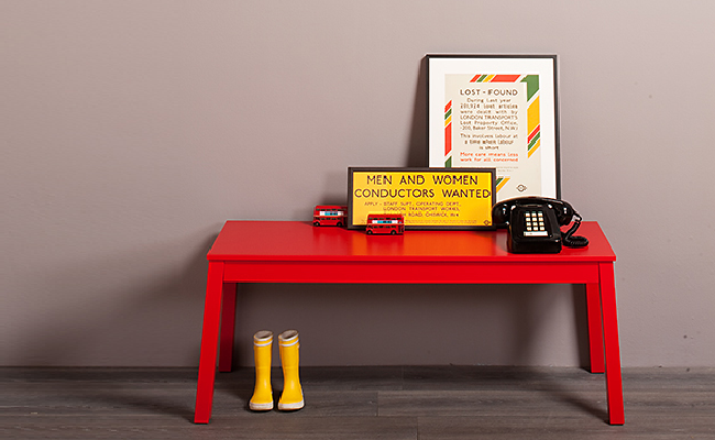 A red table with two posters, a telephone and a pair of yellow wellies