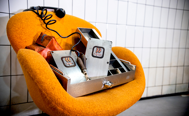 An orange chair with a metal money box, a telephone and two Jubilee line buttons